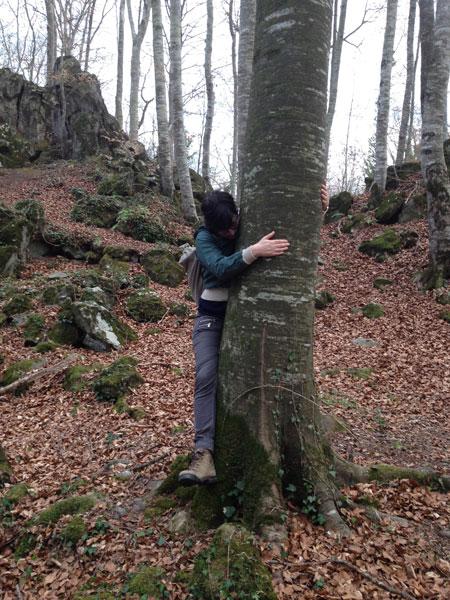 Una chica abraza un árbol en La Fageda d'en Jordà